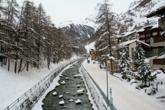 A river will snow covered rocks runs through the village.
